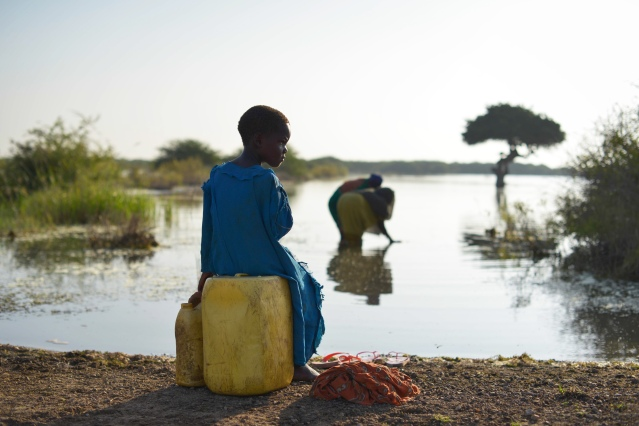 A young girl sits on a jerry can, as her mother fills up another with water, near the town of Jowhar, Somalia. (Photo Credit: UN Photo/Tobin Jones)