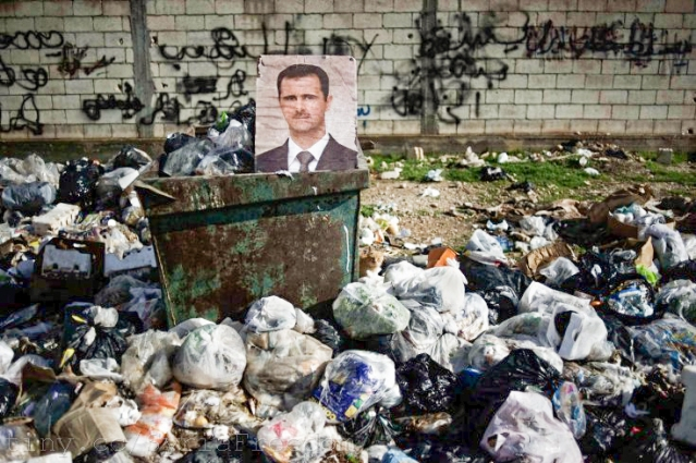 A portrait of Syrian President Bashar al-Assad among the trash in al-Qsair (Photo Credit: Freedom House)